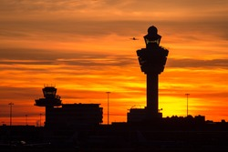 Plane taking off from Schiphol international airport at sunset. Amsterdam, The Netherlands