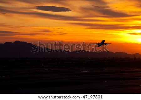 Plane taking off into red sunset.
