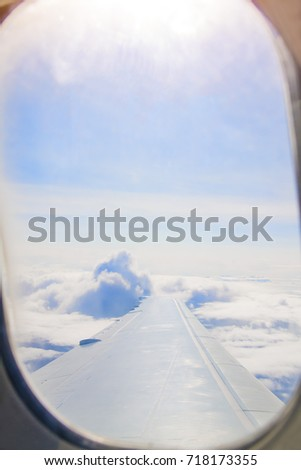 Plane window view with a wing and white clouds in the sky #718173355