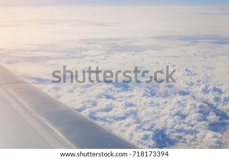 Plane window view with a wing and white clouds in the sky #718173394