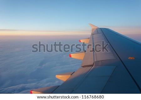 Plane wing softly illuminated by beautiful sunset.Cloudy sky