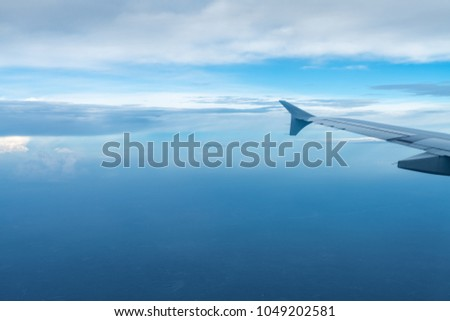 plane wing view in the sky, taking an airplane trip #1049202581