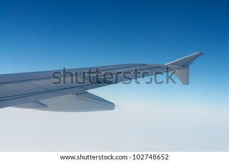 Plane wing with blue sky and clouds.