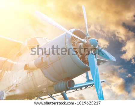 plane with propeller on beautiful bright sunset sky background
