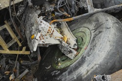 Plane wreckage, parts of the fuselage and landing gear with the wheel of the burned and broken aircraft at scrapyard of non-ferrous scrap metal for recycling.