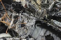 Plane wreckage, parts of the fuselage of a burned and broken aircraft at a non-ferrous scrap dump for recycling.