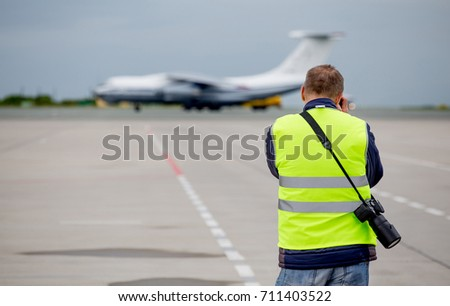 Planespotter make a photo of the airplane. Modern commercial passenger plane on background.