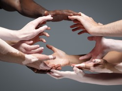 Planet Earth. Hands of different people in touch isolated on grey studio background. Concept of relation, diversity, inclusion, community, togetherness. Weightless touching, creating one unit.