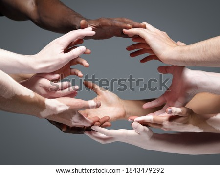Planet Earth. Hands of different people in touch isolated on grey studio background. Concept of relation, diversity, inclusion, community, togetherness. Weightless touching, creating one unit. Foto d'archivio ©