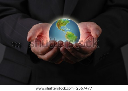 Planet earth in businessman's hands with dark background