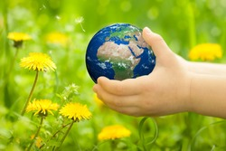 Planet Earth in children`s hands against spring flowers. Elements of this image furnished by NASA