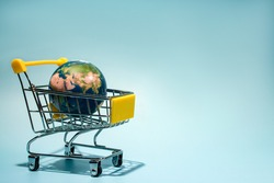 planet earth in supermarket trolley, online shopping. Concepth photo of Earth Day
