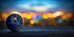 Planet Earth on the background of blurred lights of the city. Concept on business, politics, ecology and media. Earth day abstract background. Elements of this image furnished by NASA