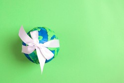 Planet Earth with white on a green background. Copy space for text.  Ecology, environmental protection. World Earth Day concept.