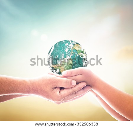 Planet in father & son hands. Human Rights Day World Health Care Mission Cancer CSR Earth Hour Adam Spring Time Autism Awareness Jesus Global Charity concept. Elements of this image furnished by NASA