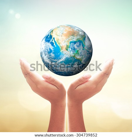 Planet in human hand over blurred nature background. Environment, Earth Day, World Environment Day and Creation from God concept. Elements of this image furnished by NASA.