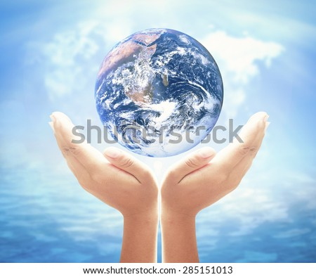 Planet in human hand over blurred world map of clouds and oceans background. Environment, Earth Day, World Environment Day and Creation from God concept. Elements of this image furnished by NASA.