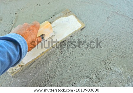 Planing fresh cement by using wooden trowel in the site