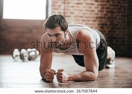 Plank it! Confident muscled young man wearing sport wear and doing plank position while exercising on the floor in loft interior #367087844