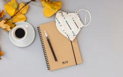 Planner for 2021. Notebook, mask, and pen on the desk table with coffee. Top view, flat lay.