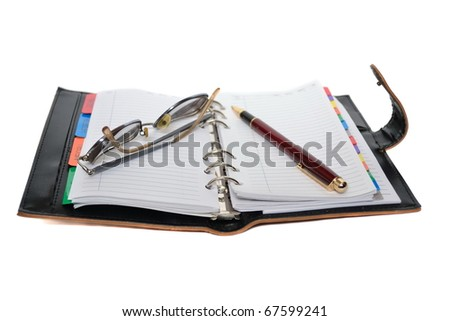 Planner, pen and eyeglasses