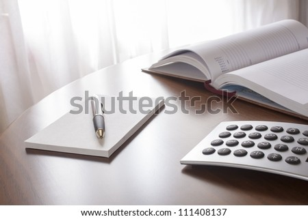 planner with  pen and calculator on the table
