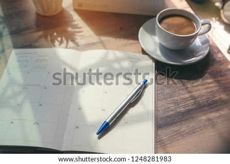 Planner write meeting agenda at Calendar book, work online at home. Diary for organizer to plan timetable, daily appointment, and management job at office desk. Planner book and 2021 Calendar Concept Stock photo ©
