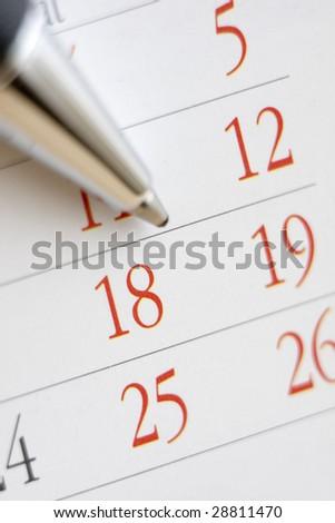 Planning future tasks on a calendar using a ballpoint pen.