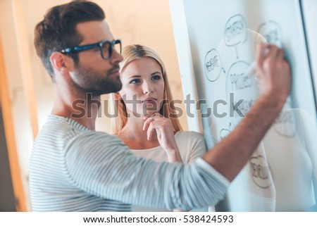 Planning is a key to success. Confident young man sketching on whiteboard while woman standing close to him and holding hand on chin