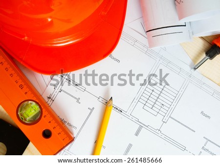 Planning of construction of the house. Repair work. Drawings for building, helmet, ruler and others tools on wooden background.