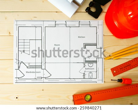 Planning of construction of the house. Repair work. Drawings for building, screwdriver, helmet and others tools on wooden background.