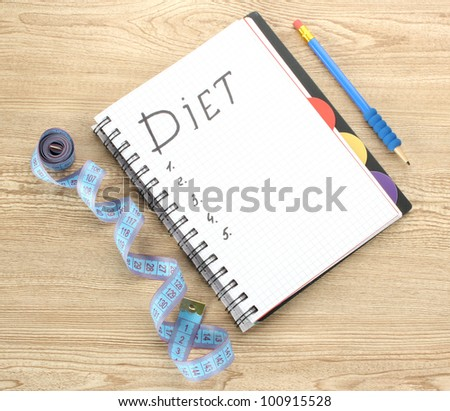 Planning of diet. Notebook measuring tape and pen on wooden table