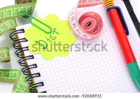 Planning of diet. Notebook measuring tapes and pen isolated on white