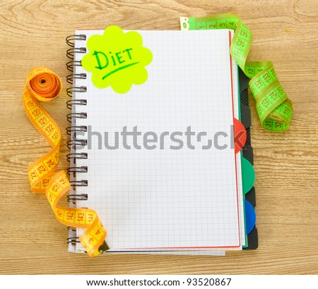 Planning of diet. Notebook measuring tapes and pen on wooden table