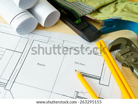 Planning of repair of the house. House construction. Drawings for building, wrench, gloves and others tools on wooden background.