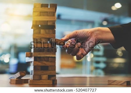 planning, risk and strategy in business, businessman gambling placing wooden block on a tower - blur for background