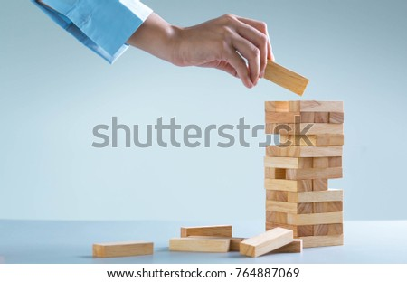 planning, risk and strategy in business, businessman gambling placing wooden block on a tower #764887069