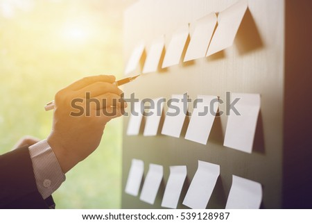 Planning, risk and strategy of project management in business, businessman putting his ideas on white board during a presentation in conference room. Focus in hands with pen writing in flipchart #539128987