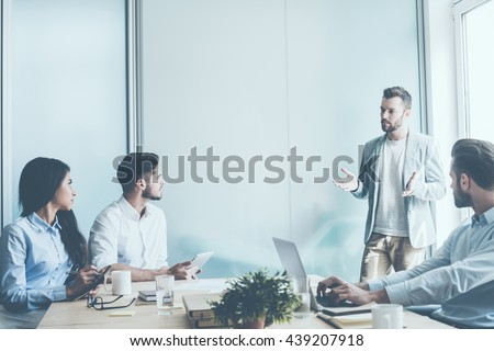 Planning strategy. Tree young business people sitting at the office desk while one man standing near them and gesturing  #439207918