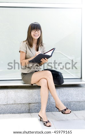 Planning the Day Ahead. Young businesswoman holding her diary on hand.