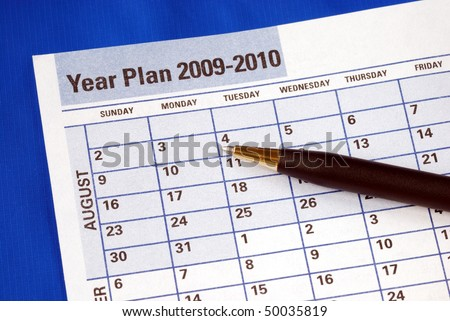 Planning the year on the day planner isolated on blue
