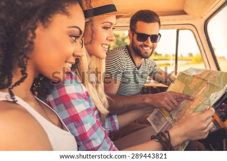 Planning their road trip. Side view of three cheerful young people examining map and smiling while sitting inside of their minivan #289443821