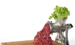 Plant-based meat concept. Green leaves of lettuce salad are inserted into the meat grinder from above, red ground beef comes out of the meat grinder on a wooden cutting board. Copy space for your text