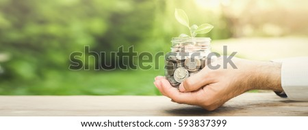Plant growing from money (coins) in the glass jar held by a man's hands  - business and financial metaphor concept, web banner with copy space