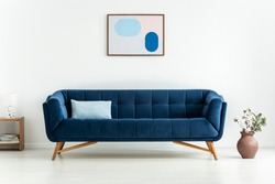 Plant next to blue settee with cushion in white minimal living room interior with poster. Real photo