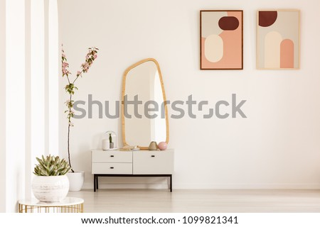 Plant on table and mirror on white cabinet in simple living room interior with posters. Real photo. Place for your furniture #1099821341
