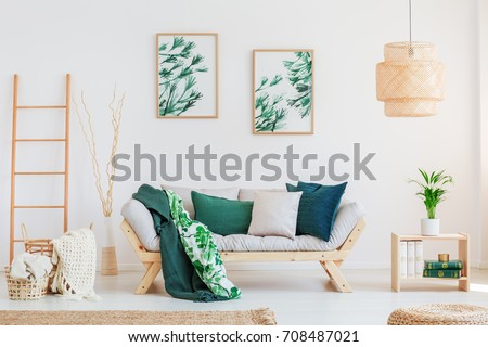 Plant on wooden table in neutral living room with green pillows on beige sofa and paintings on wall