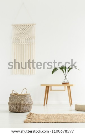 Plant on wooden table next to a basket in white boho interior with beige carpet #1100678597