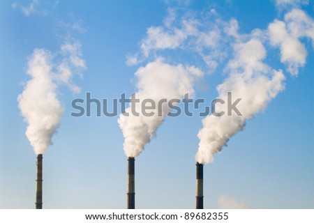 plant pipe with smoke against blue sky