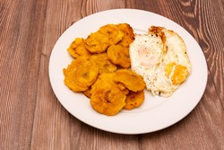 Plantain and fried eggs. Typical Cuban and Caribbean food served in white plate on wooden table.